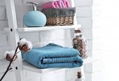 Clean towels with soap dispenser on shelves in bathroom poster