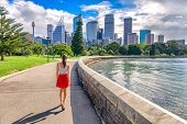Sydney city girl tourist walking in urban park with skyscrapers skyline in the background. Australia poster