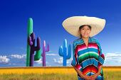 Mexican poncho girl with big sombrero in cactus background of Mexico