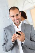 foto of young men  - Portrait of businessman using mobile phone - JPG