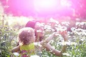 Woman And Child Smile On Sunny Floral Landscape poster