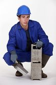 stock photo of cinder block  - Worker holding a cinder block and trowel - JPG