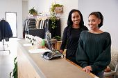 Two women smiling behind the counter in clothing store poster