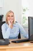 Ute Blonde Woman With Chin On Hand Behind A Desk Looking At Screen