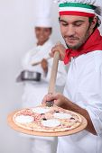Pizza man and female cook in the background