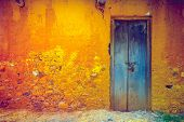 Stylish cracked vintage colorful wall in yellow orange shades with royal blue wooden door. Ideal bac poster