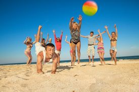foto of beach party  - Group of young joyful people playing volleyball on the beach - JPG