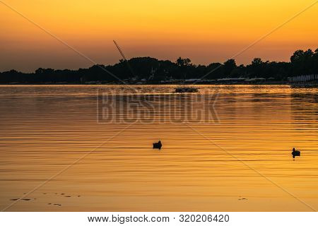 poster of Sunset On Lake Nature. Nature Lake In Sunset. Beautiful Sunset In The Nature With Duck Silhouettes.