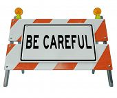 A road barricade with the words Be Careful urging you to use caution when entering a construction or