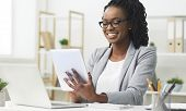 Business App. Afro Woman Using Tablet And Laptop Computer In Office. Free Space For Text poster