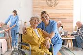 Nurse With Elderly Woman In Wheelchair At Retirement Home. Assisting Senior People poster