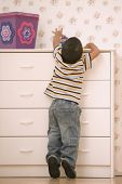 Young boy reaching on dresser