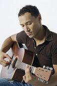 Young man strumming a guitar
