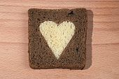 Piece Of Brown Bread With The Cut Out Heart From A White Loaf