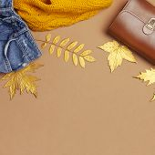 Autumn Fashion Concept. Brown Leather Women Bag, Orange Knitted Sweater, Blue Jeans, Golden Autumn L poster