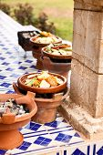 tajine ceramic cookware slow cooking over wood charcoal at outdoor restaurant morocco Africa