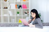 stock photo of person writing  - Attractive girl thinking and writing notes - JPG
