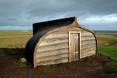 image of tyne  - Unconventional wooden boat house made from upturned ship situated on rolling fields overlooking the sea on a stormy day - JPG