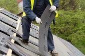 Professional And Skilled Roofer Worker In Special Protective Work Wear Installing Asphalt Or Bitumen poster