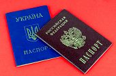 Two National Internal Passports, Red Russian Passport And Blue Ukrainian Passport On Red Background poster