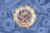 Us State Of Minnesota Flag With Transparent Dollar Banknotes In Background