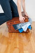 Woman Trying To Close Suitcase With Too Much Clothing