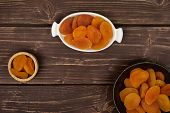 Lot Of Whole Dried Orange Apricot In Tiny Wooden Bowl In White Oval Ceramic Bowl In Dark Ceramic Bow poster