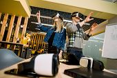Young Smiling Man And Woman In Vr Goggles Looking At Hands Excited With Augmented Reality. Couple Tr poster