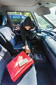 Anti Theft System Problem Concept. Burglar Thief Man Wearing Black Clothes Breaking Into Car, Steali poster