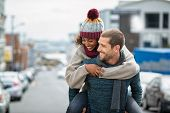 Smiling man giving piggyback ride to woman in the city. Young multiethnic couple in cold clothes wal poster