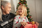 Girl sitting on grandmother lap holding christmas present. Happy granddaughter sitting with grandma  poster