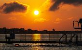 A Swimmer In A Pool That Is Located Next To The Bay During Sunrise Is Reflecting The Sun With His Sp poster