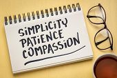 simplicity, patience, compassion - three words from Buddha teaching - handwriting in a notebook with poster