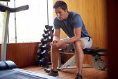 Man Anxious About Body Image Sitting On Weight Bench In Home Gym poster