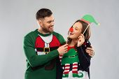 christmas, photo booth and holidays concept - happy couple in ugly sweaters posing with party props poster