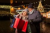 sale, winter holidays and people concept - happy senior couple with shopping bags at christmas marke poster