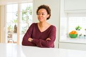 Young beautiful african american woman at home smiling looking side and staring away thinking. poster