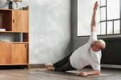 Man Doing A Side Plank Exercise At Living Room. poster