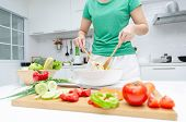 Delicious. Young Pretty Woman In Green Shirt Standing And Preparing The Vegetables Salad In Bowl For poster