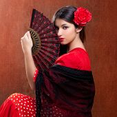 stock photo of frilly  - Gipsy flamenco dancer Spain girl with red rose and spanish hand fan - JPG