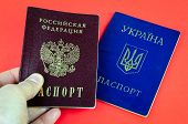 Two National Internal Passports On Red Background, Lying Blue Ukrainian Passport And Red Russian Pas poster