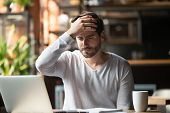 Upset Man Working In Cafe, Suffering From Headache, Touching Forehead poster