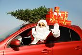 Authentic Santa Claus With Presents And Fir Tree On Roof Driving Modern Car Outdoors poster