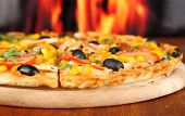 Close-up de deliciosa pizza na mesa de madeira no fundo do fogo