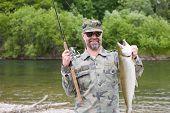 Joyful fisherman holds caught pink salmon.