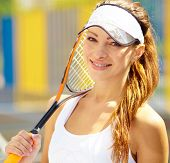 Tennis player relaxing with her racquet