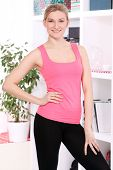 Beautiful middleaged woman in fitness wear at home