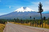 stock photo of andes  - Dirt road that leads to the majestic Cotopaxi  - JPG