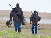 stock photo of shotgun  - Father and son out hunting in the fall - JPG