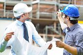 stock photo of real-estate-team  - Two engineers working in a construction site - JPG